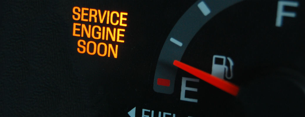 """Closeup of dashboard with """"Service Engine Soon"""" icon lit up"""