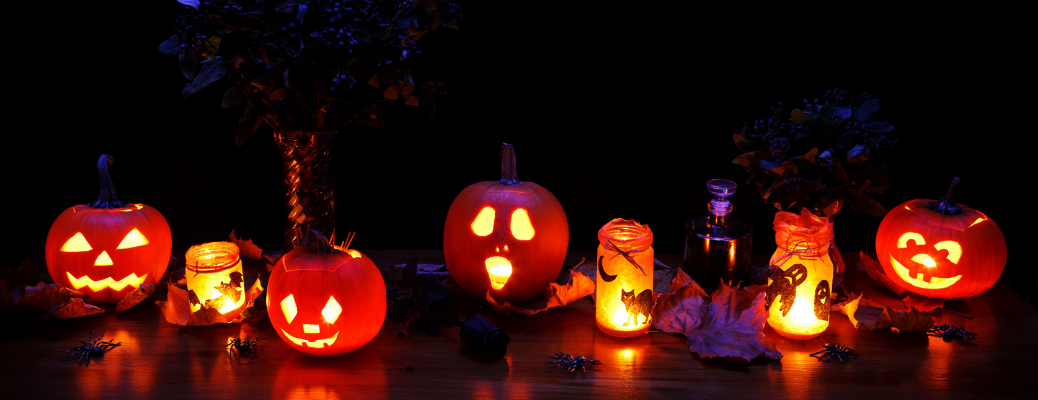 Line of Halloween jack-o-lanterns and candle