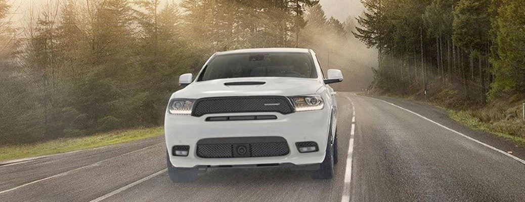 White 2020 Dodge Durango driving down a road in a forest