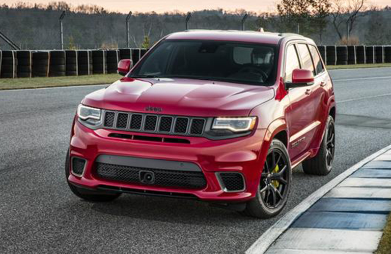 Red 2020 Jeep Grand Cherokee driving down a road