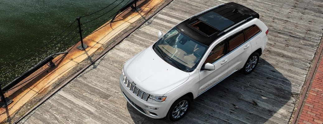 The front and top view of a white 2021 Jeep grand Cherokee on a pier.