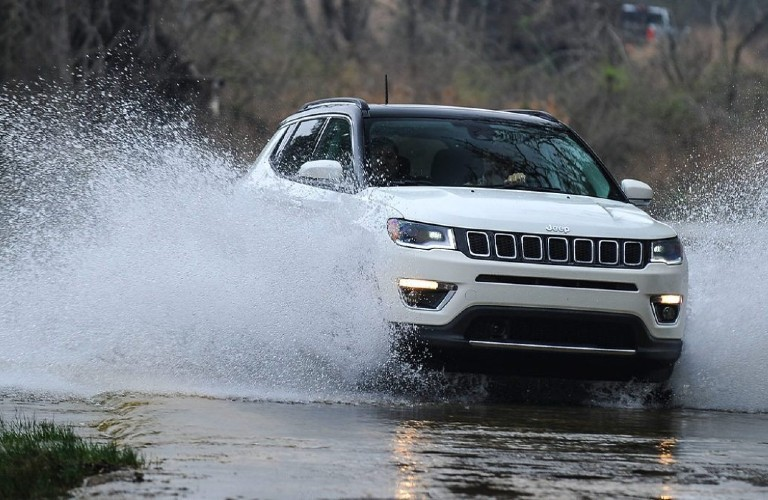 A white 2021 Jeep Compass driving over a puddle.