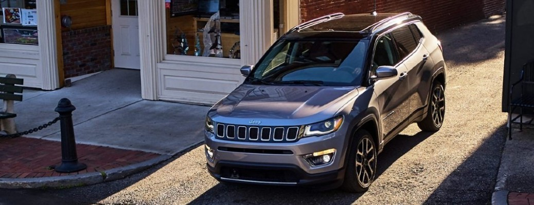 A top and front view of a gray 2021 jeep Compass turning onto a road.