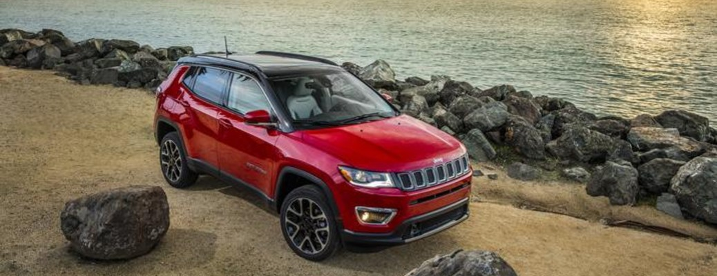 The top and side view of a red 2021 Jeep Compass driving along a coast.