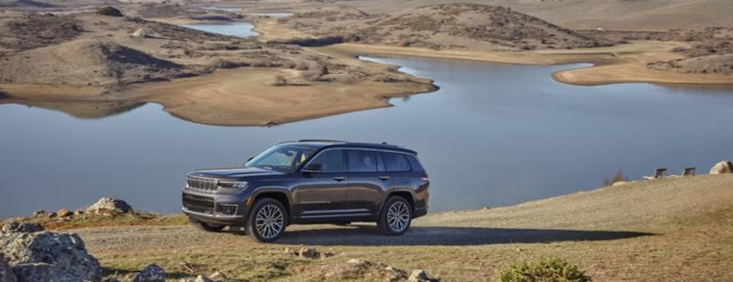 A gray 2021 Jeep Grand Cherokee parked on a ridge in front of a large valley.