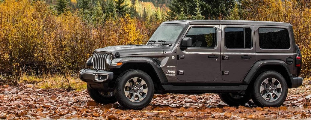 The side view of a gray 2021 Jeep Wrangler Sahara parked in an area during the fall.