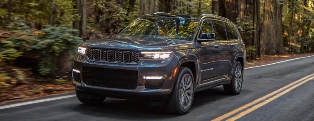 The front and side view of a 2021 Jeep Grand Cherokee L model driving down a forested road.