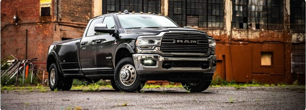 Black 2021 Ram 3500 parked in front of an old factory site
