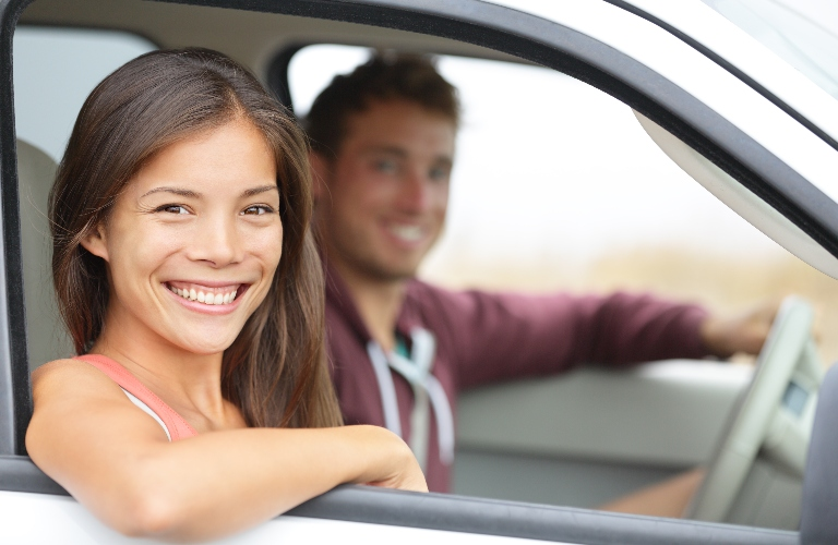 Happy couple in a new vehicle