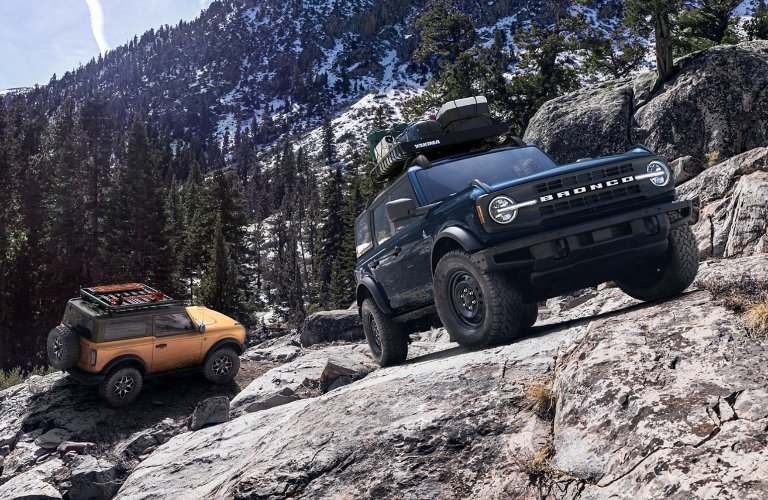 Two 2021 Ford Bronco vehicles on rocks