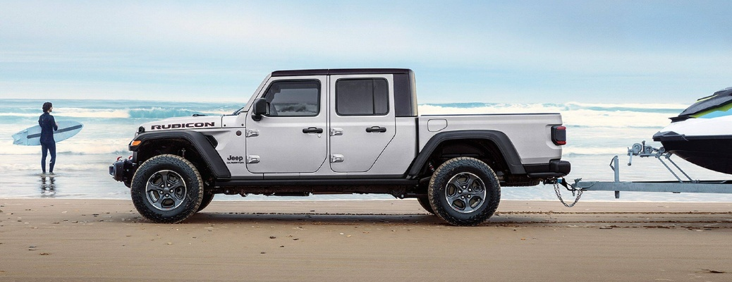 2021 Jeep Gladiator on the beach with a jet ski behind it