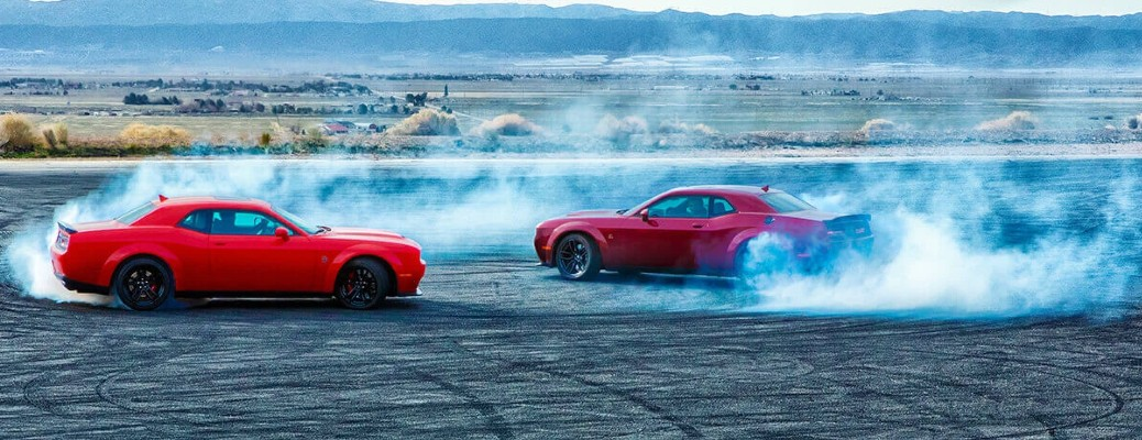 Two 2021 Dodge Challengers doing donuts