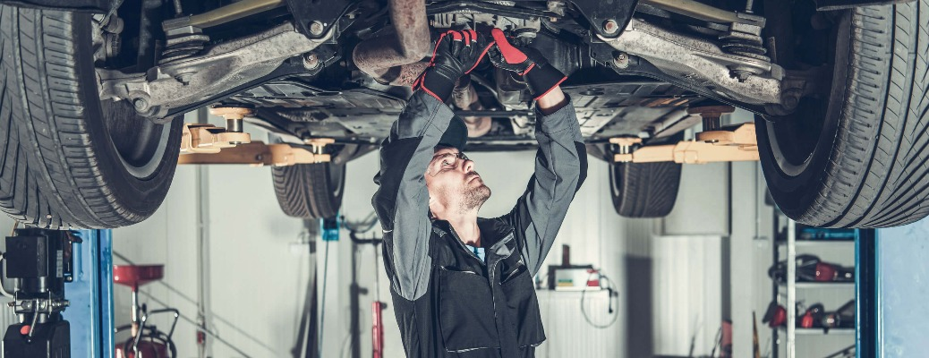 Car mechanic under a vehicle