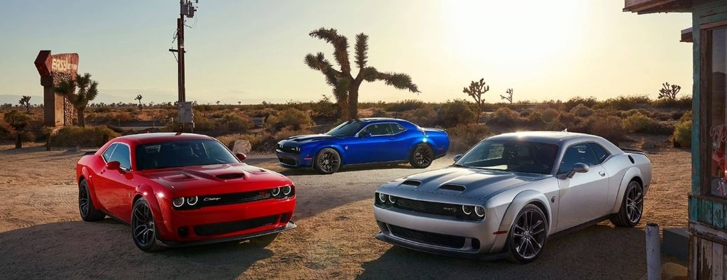 three Dodge Challengers parked in an open space