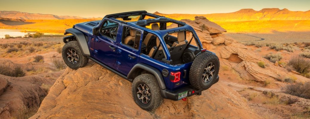 2020 Jeep Wrangler Rubicon EcoDiesel exterior shot with blue paint color and removed top parked on the top of a rocky cliff amidst desert dunes