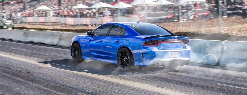 2020 Dodge Charger exterior side rear shot with Indigo Blue paint color driving down a race track as burning rubber and dust kick up