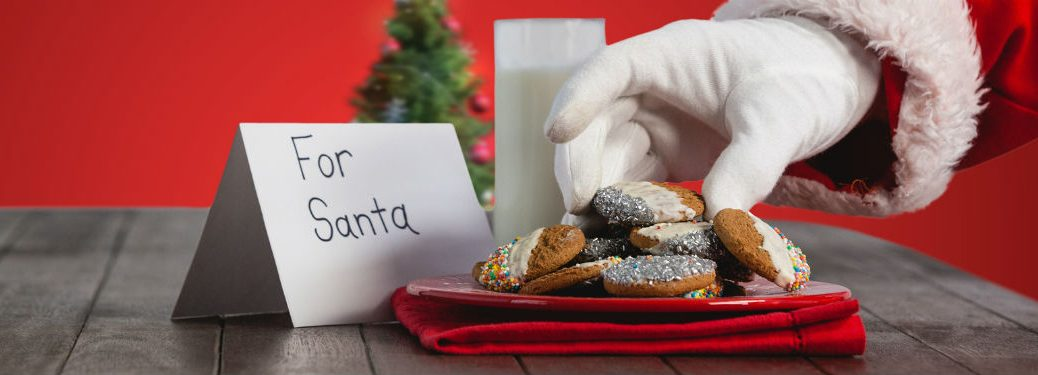 table with sign that says for santa with plate of cookies and milk with a hand reaching for cookie