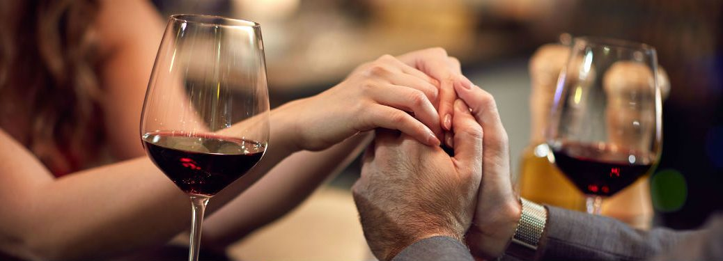 couple holding hands at restaurant two glasses of red wine on table