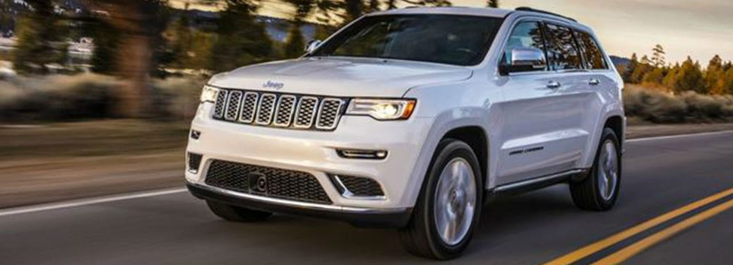 2020 Jeep Grand Cherokee white exterior front fascia driver side driving