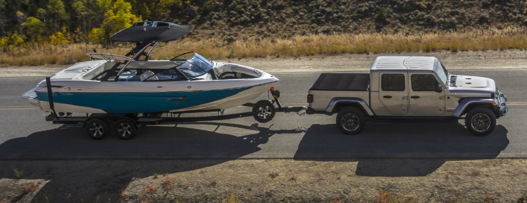2020 Jeep Gladiator passenger side driving towing a boat