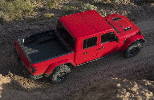 2020 Jeep Gladiator red exterior sky view passenger side driving on dirt road