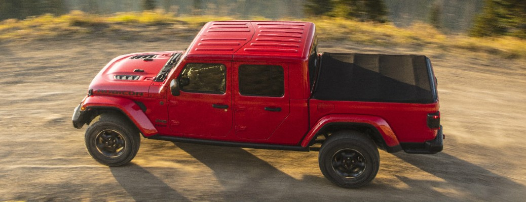 2020 Jeep Gladiator red exterior upper view of driver side driving on sandy road