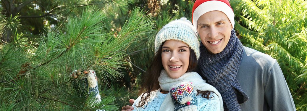 A man and a woman wearing hats and standing by a Christmas tree