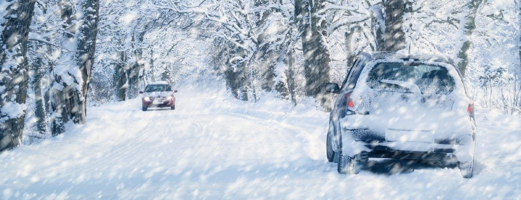Two cars driving in the snow