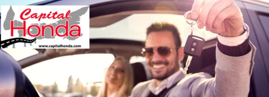 Happy Couple in a New Car Holding Keys with Capital Honda Logo in Top Left Corner