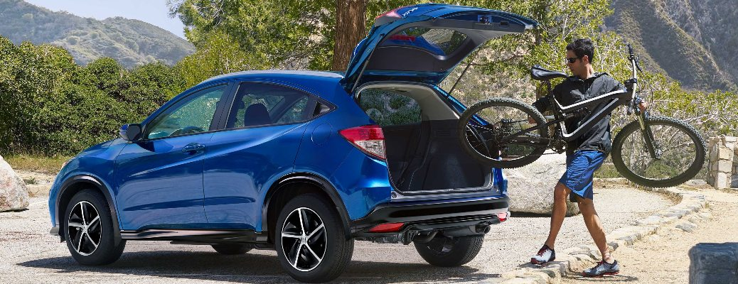 Man putting a bike in the back end of a 2021 Honda HR-V