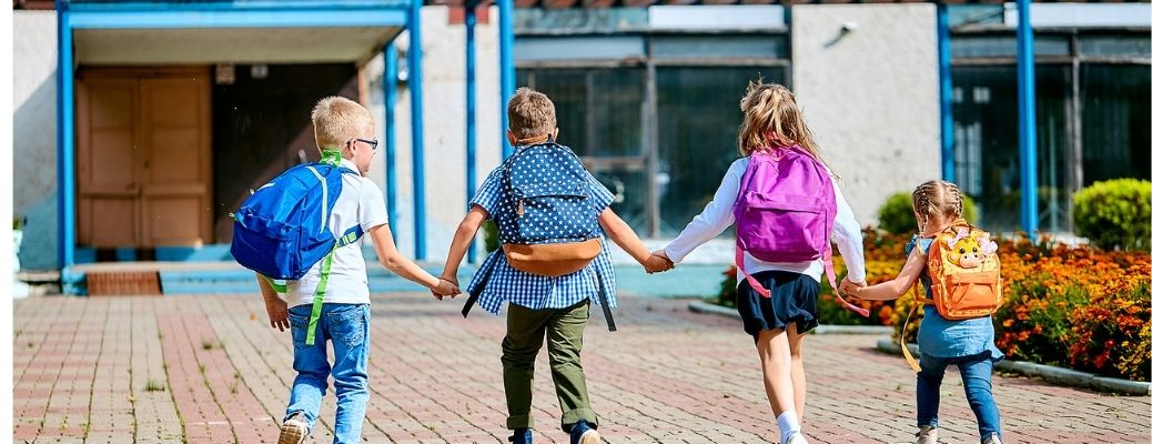Four school-going kids with backpacks on their backs going to school
