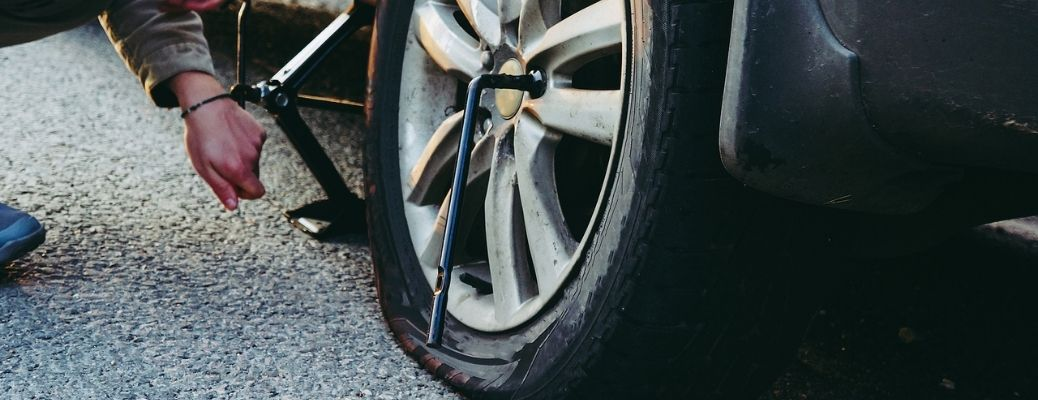 Image of a person changing a flat tire with a jack and a lug wrench in frame