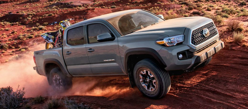 Exterior view of a silver 2018 Toyota Tacoma driving over a desert hill with an ATV in the truck bed
