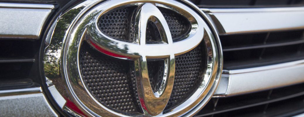 close up of Toyota logo badge on fascia and grille plating and mesh