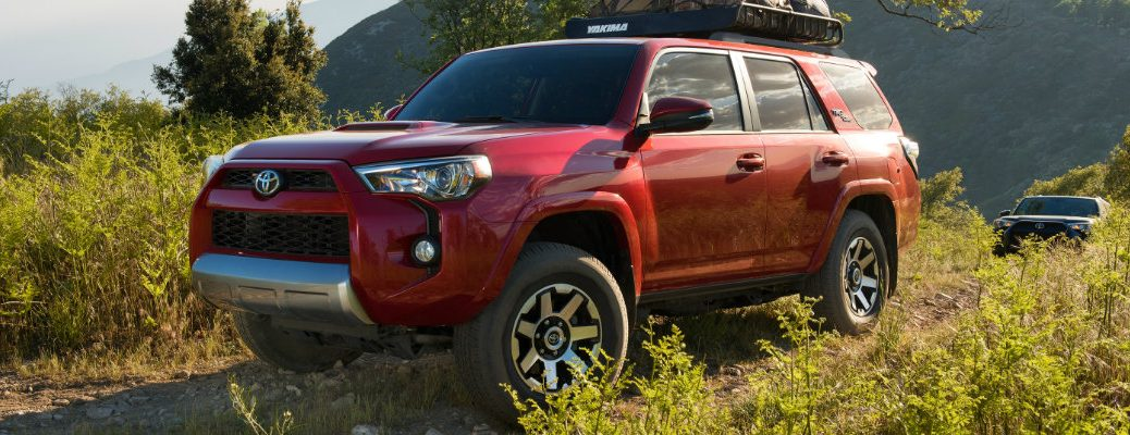 2019 Toyota 4Runner SUV exterior shot with red paint color parked on an off-road hill of tall grass with a full roof rack of luggage
