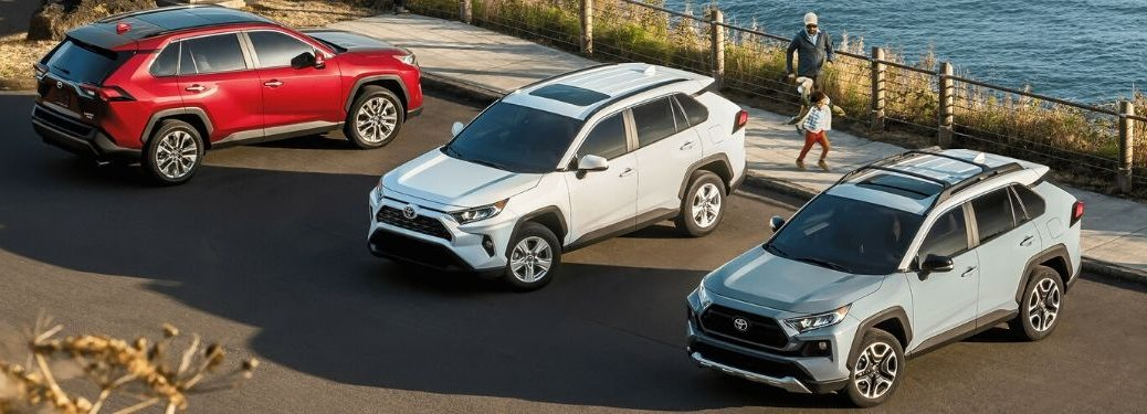 2020 Toyota RAV4 Limited, XLE and Adventure SUVs parked in front of the water