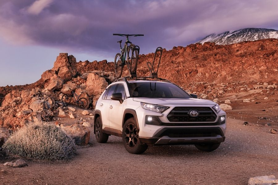 2020 Toyota RAV4 TRD Off-Road parked in front of off-road trail with bike on roof