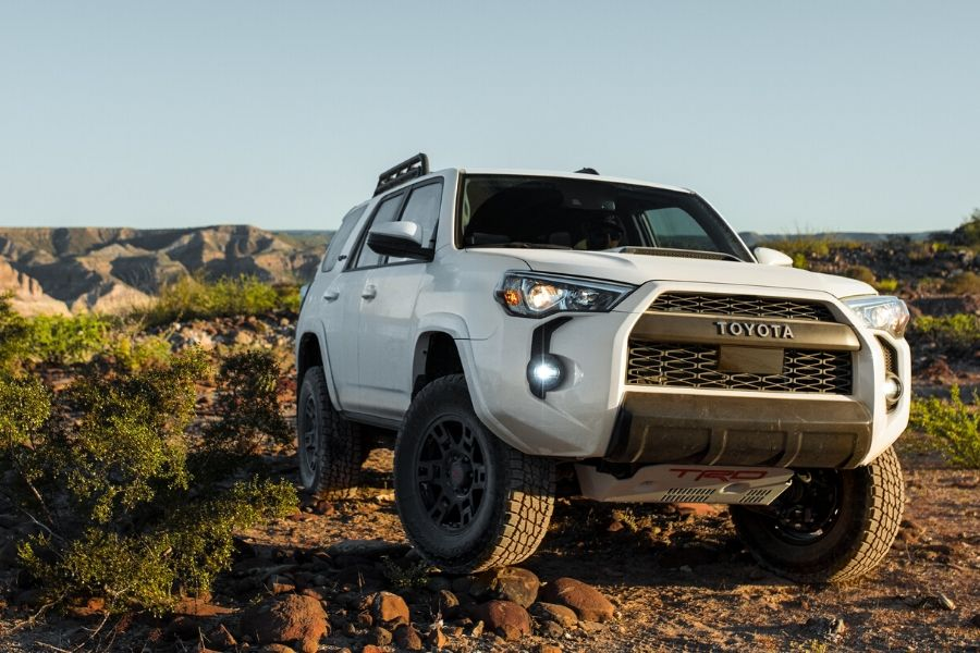 White 2020 Toyota 4Runner in field with rocks from exterior front passenger side