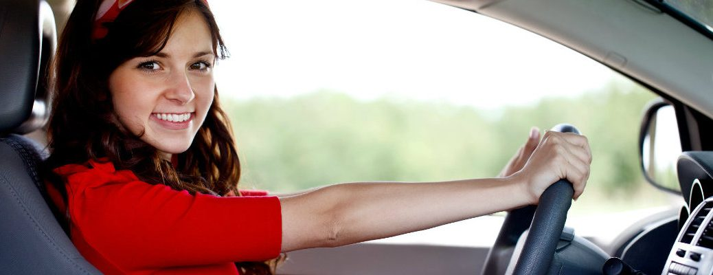 Young woman in a red dress behind the wheel of a new car