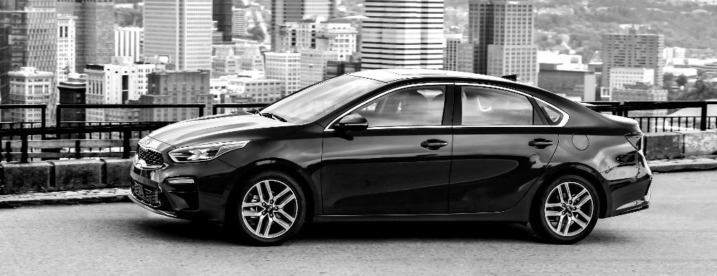 Black & white image of the 2019 Kia Forte driving through the city