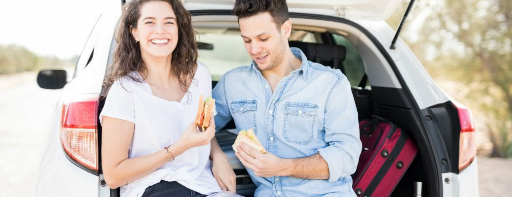 Couple eating sandwiches out of the back of their vehicle