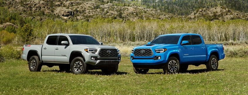 Exterior view of a white 2020 Toyota Tacoma and a blue 2020 Toyota Tacoma