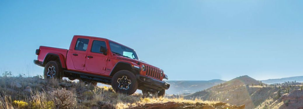 2020 Jeep Gladiator exterior front fascia and passenger side on high hill with sunlight in front