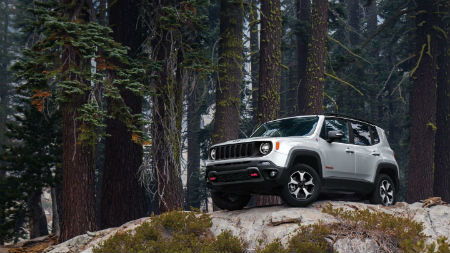 2020 Jeep Renegade exterior front fascia and driver side low view on rocks with forest behind it
