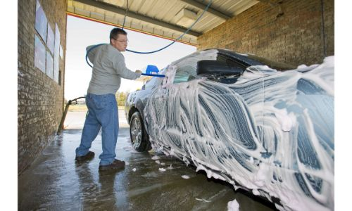 Man washing his car with a brush