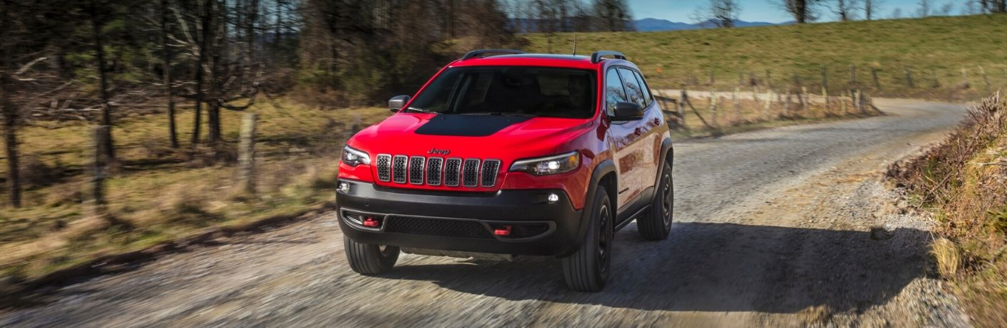 Red 2020 Jeep Cherokee driving on a gravel road