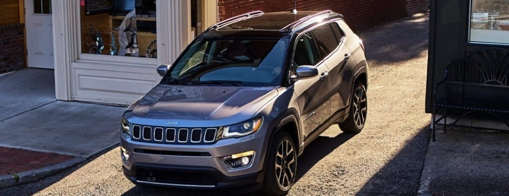 A 2021 Jeep Compass driving outside between two buildings