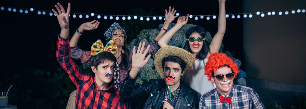 Five friends with humorous Halloween outfits each including a fake mustache