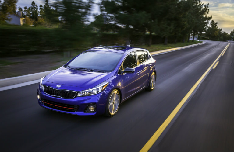 blue 2018 kia forte driving down highway