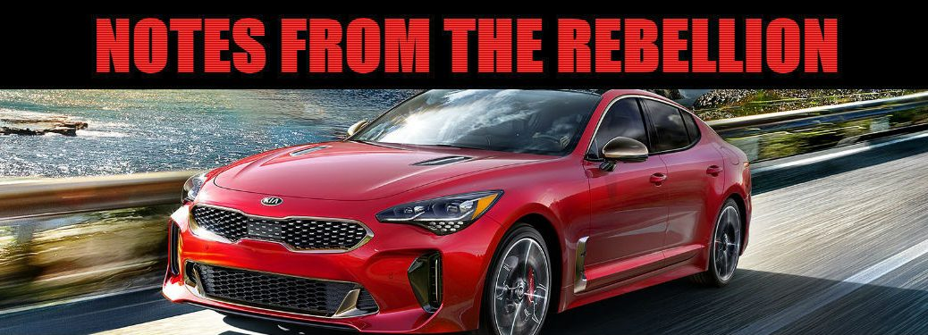 "2019 Kia Stinger GT in red driving on highway with text ""notes from the rebellion"" above"